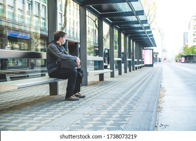 Caucasian man, with mask on his face sitting at a bus stop and waiting for a public transportation
