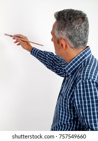 Caucasian man of middle age with grey hair holding paintbrush and demonstrating how to measure and paint, isolated on empty white background, copy space
