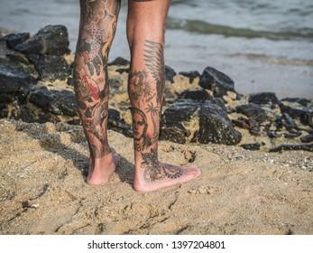 Caucasian man on the beach. Detail of his legs with tattoo. Mirissa, Sri Lanka, March 17, 2019.