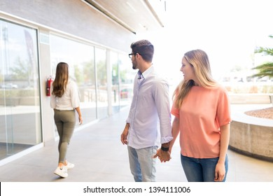 Caucasian man paying attention to other female while roaming in shopping mall with girlfriend