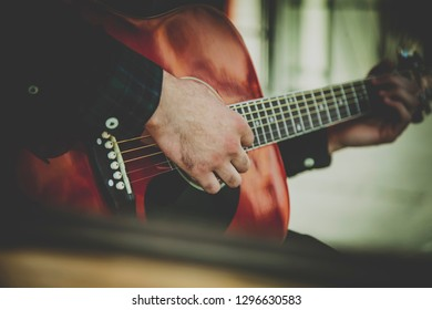 Caucasian man playing the guitar outdoors. Music, art, creativity concept. Image retro styled.