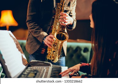 Caucasian man playing saxophone in home studio while young talented woman playing clavier.