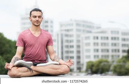 Caucasian man practicing yoga in lotus pose in city center