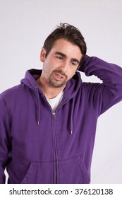 Caucasian man in purple sweatshirt with a hood, looking thoughtful