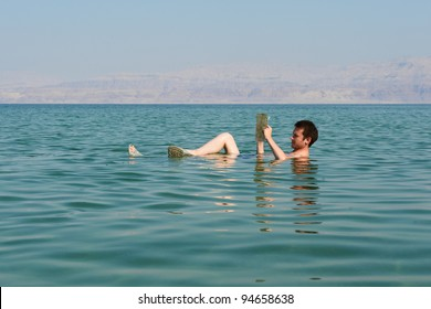 Caucasian man reads a book floating in the waters of the Dead Sea in Israel