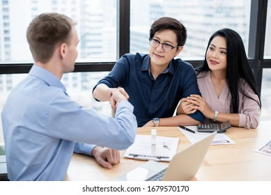 Caucasian man realtor hand shake with couple who are sign contract of rent or buy property. Real estate agent, property trade business, financial investment planning concept.