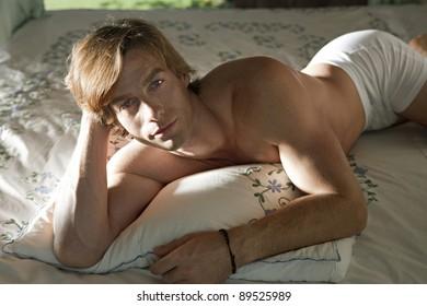 Caucasian man relaxing in bed.