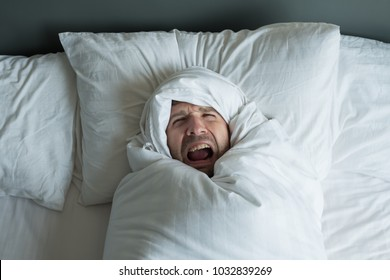 caucasian man rolled in white blanket. He shouts because had terrible nightmare. Concept of problems with mental health