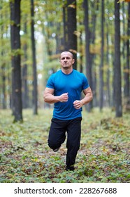 Caucasian man running in the forest, outdoor fitness concept