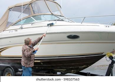 Caucasian man scrubbing power boat with brush