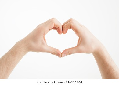 A caucasian man shows a heart symbol with his fingers.