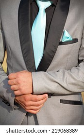 Caucasian man in a silver-grey formal suit with black trimmings. His hands are shown in front of his waist. He is wearing a turquoise tie and pocket handkerchief.