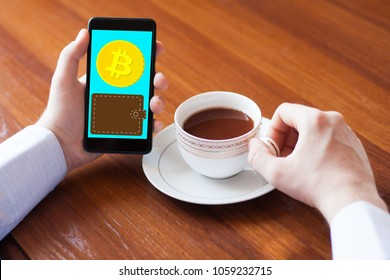 Caucasian man sitting in internet caffe sipping coffee and going to pay via mobile application. Cryptocurrency bitcoin cyber pay application. Closeup view of phone screen,