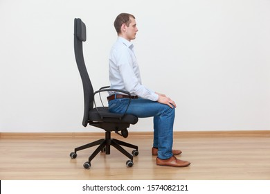 caucasian man sitting on the edge of office chair in correct posture