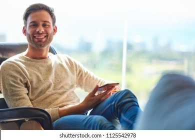 Caucasian man sitting on a modern couch next to large glass windows with a stunning view behind him as he smiles at camera with his phone still being held in his hands.