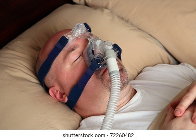 Caucasian man with sleep apnea using a CPAP machine in bed.