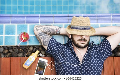Caucasian man sleep sunbath and listening music beside the pool