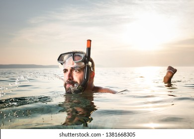 Caucasian man snorkeling, floating on the surface, spitting out water with a funny goofy facial expression, summer seaside vacation activity