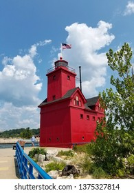Caucasian man standing by bright red lighthouse on pier in Holland Michigan harbor