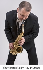 Caucasian Man in Suite Playing the Saxophone. Posing Against White. Vertical Image Orientation