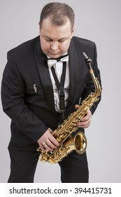 Caucasian Man in Suite with Saxophone. Posing Against White. Vertical Image