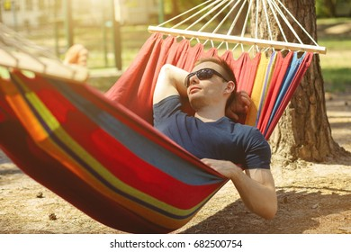 Caucasian man with sunglasses lying on hammock in a pine forest. Outdoors relaxation.