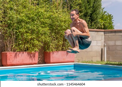 Caucasian man takes a bomb dive in the pool