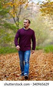 Caucasian man taking a walk in the forest, autumnal landscape