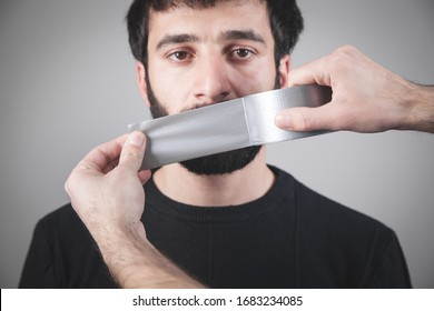 Caucasian man with tape on mouth. Censorship