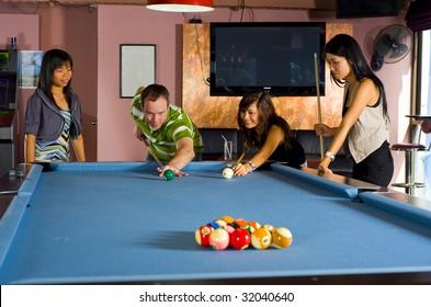 a caucasian man teaching pool to asian women