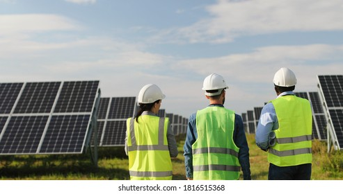 Caucasian man tellng woman and African-American man about working on solar farm. Woman holding paper plan in her hands. Three engineers in uniform.