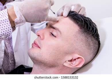 Caucasian man undergoing beauty spa botulinum neurotoxin Botox treatment for anti-aging, to smooth wrinkles as a cometic solution. Injecting forehead to relax muscles with a non-invasive procedure.