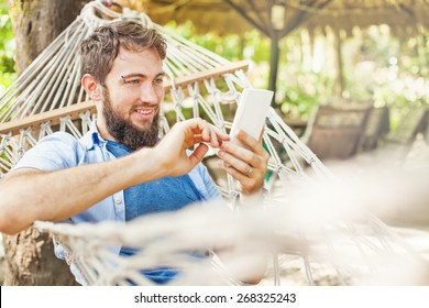 caucasian man using an app on his mobile phone white swinging in a hammock