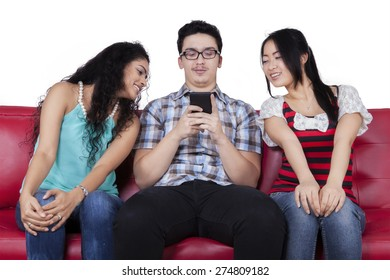 Caucasian man using mobile phone to send message near the curious friends