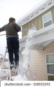 Caucasian man using rake to shovel heavy snow off roof