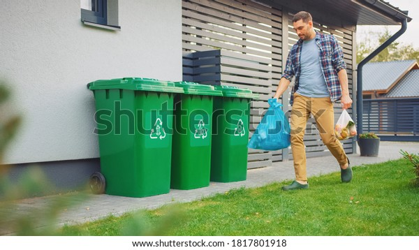 Caucasian Man is Walking Outside His House in Order to Take Out Two Plastic Bags of Trash. One Garbage Bag is Sorted as Biological Food Waste, Other is Recyclable Bottles Garbage Bin.