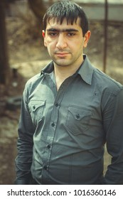 Caucasian man walking in the Park. Armenian guy in business clothes. emotional portrait. thick eyebrows and short hair. posing against the backdrop of the urban landscapes of the city