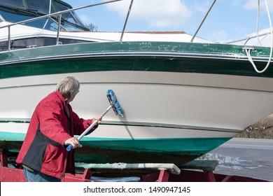 Caucasian man washing boat hull with blue brush