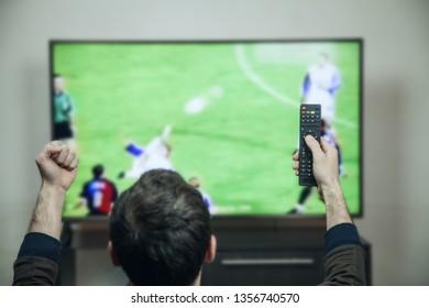 Caucasian man watching football on smart tv.