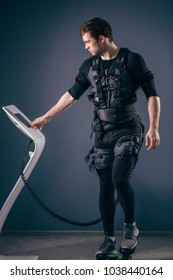 Caucasian man wearing biometric fitness vest training on stepper with electric muscle stimulation