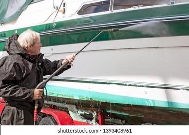 Caucasian man wearing black waterproof suit while power washing dirty boat hull