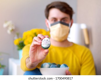Caucasian man wearing self protection face mask holding an easter egg with a face mask during easter time, coronavirus outbreak time, with yellow sweather and flowers in the background.