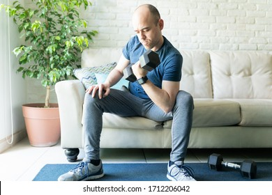 Caucasian man wearing a smartwatch sitting in a sofa at home and doing bicep curls and lifting weights