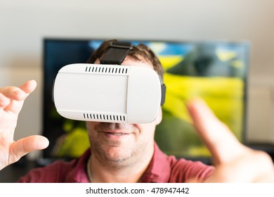 Caucasian man wearing VR headset glasses in front of tv screen making gestures