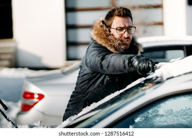 Caucasian man wearing warm jacket removes snow from vehicle, cleaning after snow blizzard