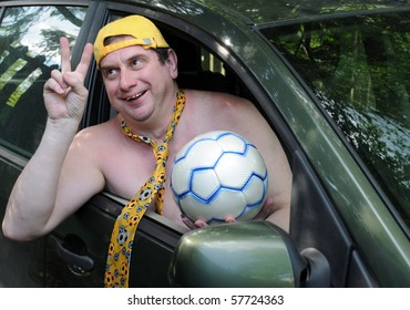 Caucasian man wearing a yellow baseball cap and a yellow tie without a shirt is hanging out of the car window showing a V-sign and holding a soccer ball.