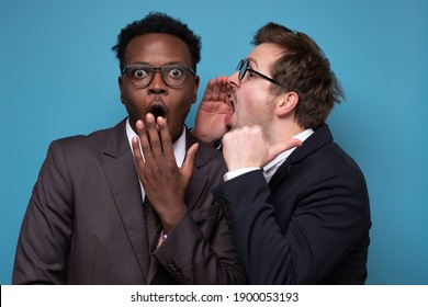 Caucasian man whispering to his african coworker ear telling him something secret. Studio shot on blue wall. Human emotions facial expressions