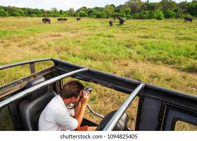 Caucasian man in white shirt making photos of elephant herd during safari in national park of Sri Lanka. Active traveling in vacation in asia
