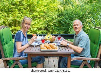 Caucasian man and woman eating lunch on terrace in nature