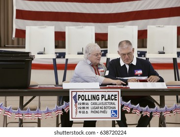 Caucasian man and woman working at polling place